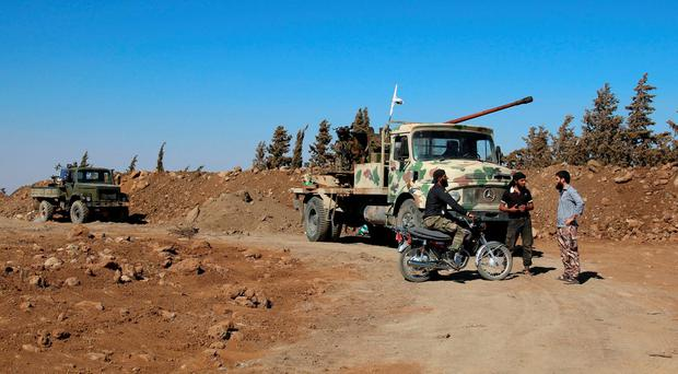 Rebel fighters gather near military vehicles in Quneitra countryside, Syria September 10, 2016. REUTERS/Alaa Al-Faqir