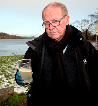 Toxic: Jim Cusack with a sample of contaminated water from a stream near Castleblaney in Co Monaghan Photo: Sunpix