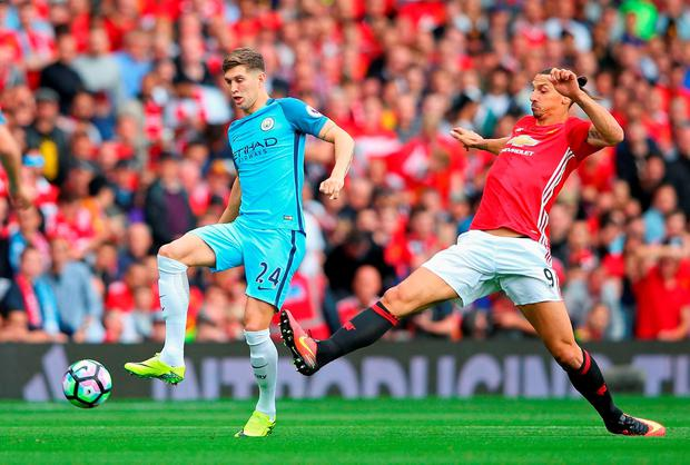 Zlatan Ibrahimovic of Manchester United is tackled by John Stones of Manchester City. (Photo by Alex Livesey/Getty Images)