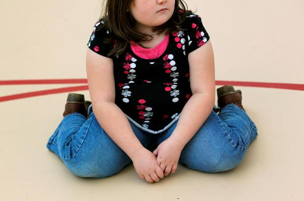 A child sits on the gym floor during a program for overweight children. Photo by John Moore/Getty Images