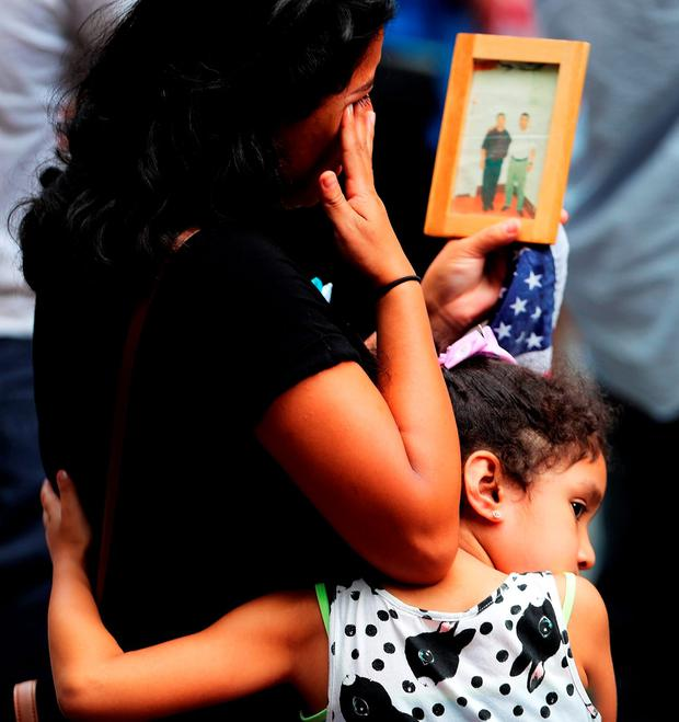 A young girl holds her mother during a commemoration ceremony at the 9/11 event in New York. Photo by Spencer Platt/Getty Images