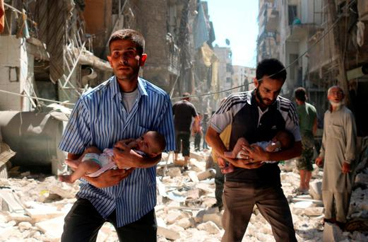 Syrian men carrying babies make their way through the rubble of destroyed buildings following a reported air strike on a rebel-held neighbourhood of Aleppo. Photo: AFP/Getty Images