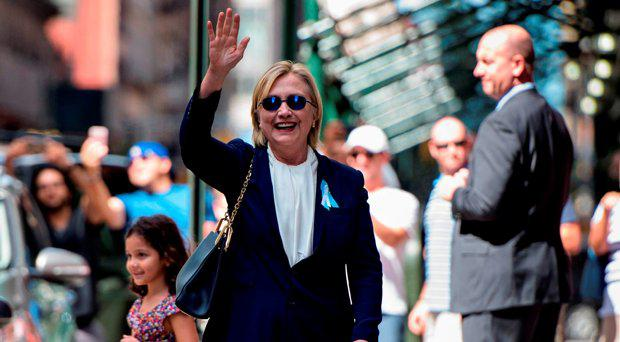 US Democratic presidential nominee Hillary Clinton waves to the press as she leaves her daughter's apartment building after resting on September 11, 2016, in New York