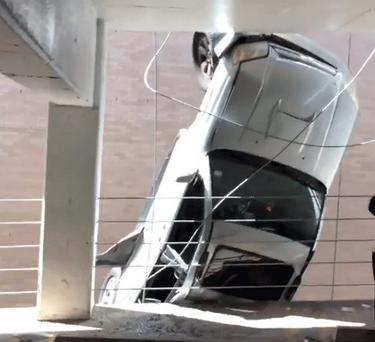The car dangling off the side of the building