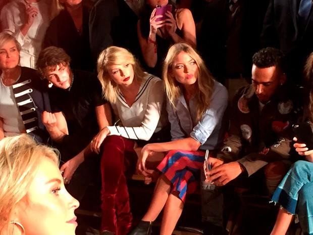 TV personality Yolanda Hadid, seated from left, model Anwar Hadid, singer Taylor Swift, model Martha Hunt and Formula One racer Lewis Hamilton at the the Tommy Hilfiger Fall 2016 collection at Fashion Week in New York, Friday, Sept. 9, 2016. (AP Photo/Nicole Evatt)