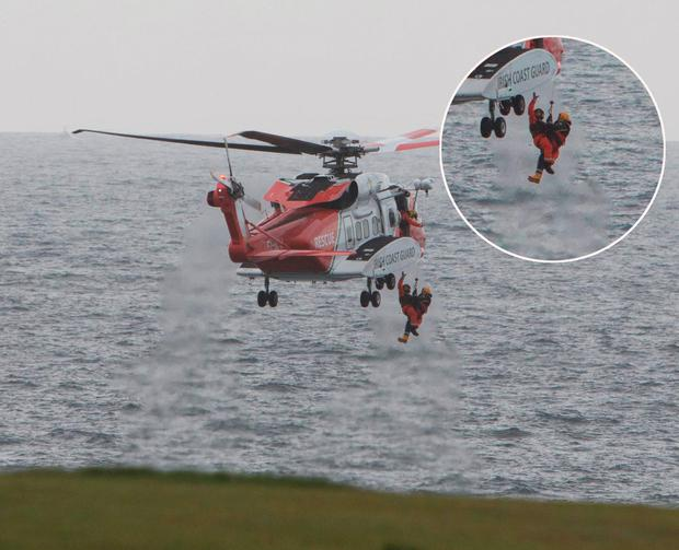A man (left) is air lifted from the sea after he became trapped in a cave below the cliffs in Kilkee, Co Clare where he sheltered when his boat capsized while searching for a man missing since Friday. Credit: Press 22