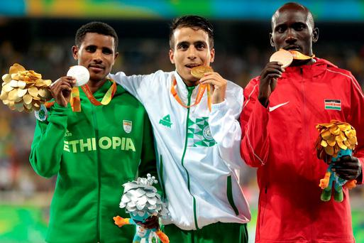 Silver medalist Tamiru Demisse of Ethiopia, gold medalist Abdellatif Baka of Algeria and bronze medalist Henry Kirwa of Kenya celebrate on the podium at the medal ceremony