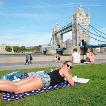 A woman sunbathes near City Hall, on the South Bank in London. Photo: John Stillwell/PA Wire