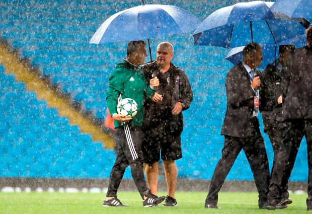 Referee Bjorn Kuipers and head groundsman Lee Jackson inspect the pitch. Photo: Martin Rickett/PA Wire