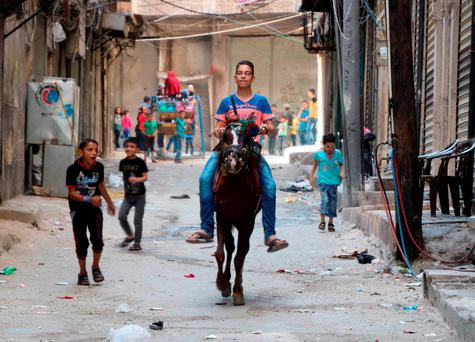 A Syrian boy rides a horse as Syrian children play in the street in the northern Syrian city of Aleppo as they celebrate the Eid al-Adha holiday on the first day of a fragile ceasefire. Photo: AFP/Getty Images