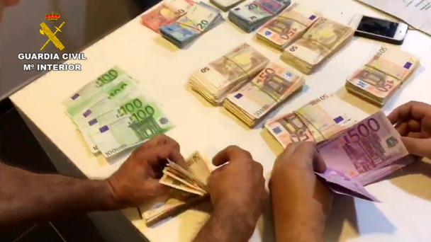 Police count wads of money seized at the gym