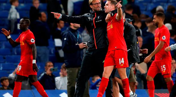 Liverpool manager Jurgen Klopp (left) and Liverpool's Jordan Henderson celebrate after the final whistle during the Premier League match at Stamford Bridge, London. PRESS ASSOCIATION Photo. Picture date: Friday September 16, 2016. See PA story SOCCER Chelsea. Photo credit should read: Scott Heavey/PA Wire. RESTRICTIONS: Editorial use only. Maximum 45 images during a match. No video emulation or promotion as 'live'. No use in games, competitions, merchandise, betting or single club/player services. No use with unofficial audio, video, data, fixtures or club/league logos.