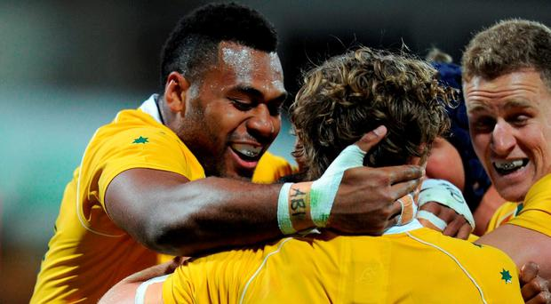 Australian players celebrate the try of Will Genia (obscured) during the Rugby Championship match between Australia and Argentina in Perth