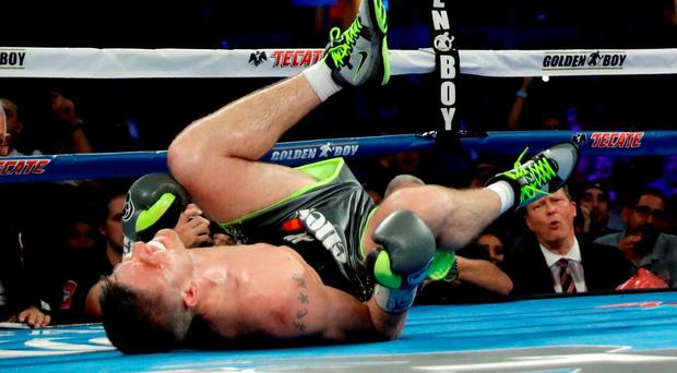 Liam Smith grimaces after being knocked down by Canelo Alvarez during the WBO Junior Middleweight World fight at AT&T Stadium
