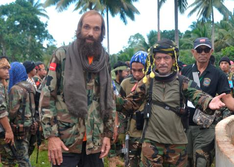 Moro National Liberation Front (MNLF) leader Nur Misuari (front R) escorts former hostage Norwegian national Kjartan Sekkingstad (front L) after he was freed from the al Qaeda-linked Abu Sayyaf Islamist militant group. REUTERS/Nickie Butlangan