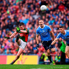 Mayo's Cillian O'Connor kicks his side's equalising point despite the best efforts of Dublin players Eoghan O'Gara and Darren Daly. Photo: Daire Brennan/Sportsfile
