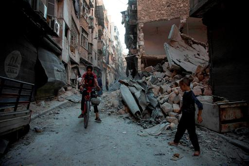 Locals make their way through the rubble following an airstrike in Aleppo yesterday. Photo: Getty Images