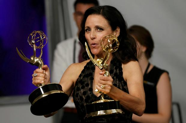 Actress Julia Louis-Dreyfus poses backstage with her awards for Outstanding Comedy Series and Outstanding Lead Actress In A Comedy Series for her role in HBO's