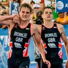 British athlete Alistair Brownlee (L) helps his brother Jonathan Brownlee (R) before crossing the line in second and third place during the ITU World Triathlon Championships 2016 in Cozumel, Quintana Roo, Mexico