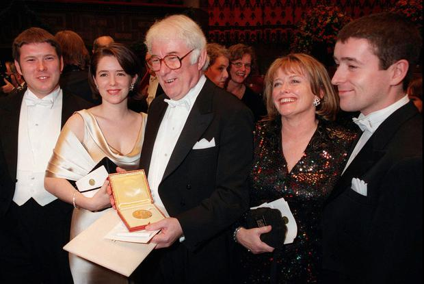 Irish poet Seamus Heaney, center, displaying his Nobel literature prize medal, surrounded by his family, from left: his son Michael, daughter Catherine, his wife Marie and son Christopher, after receiving it from the Swedish King Carl XVI Gustaf at the Concert Hall in Stockholm, Sweden.