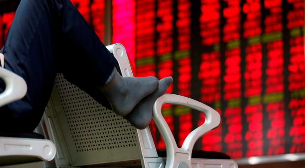 An investor puts his feet on a chair in front of an electronic board showing stock information at a brokerage house in Beijing