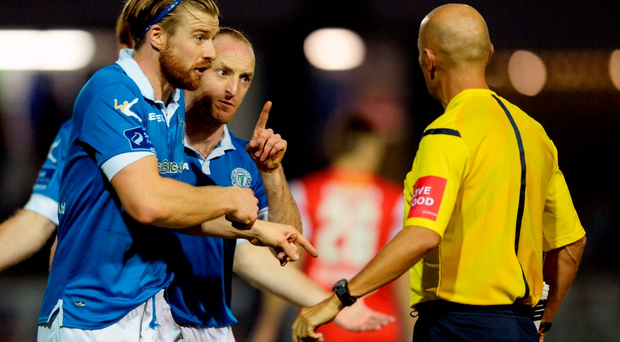 Keith Cowan and Michael Funston of Finn Harps have words with Referee Paul Tuite during the SSE Airtricity League Premier Division match between Finn Harps and Cork City