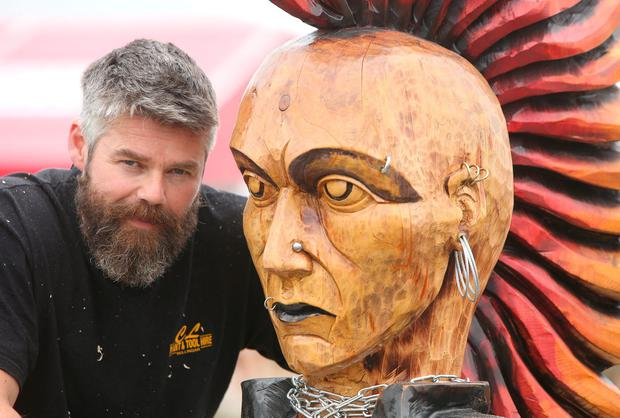 Ritchie Clarke, from Mullingar, with his wood carving of a woman with a mohawk Photos: Damien Eagers