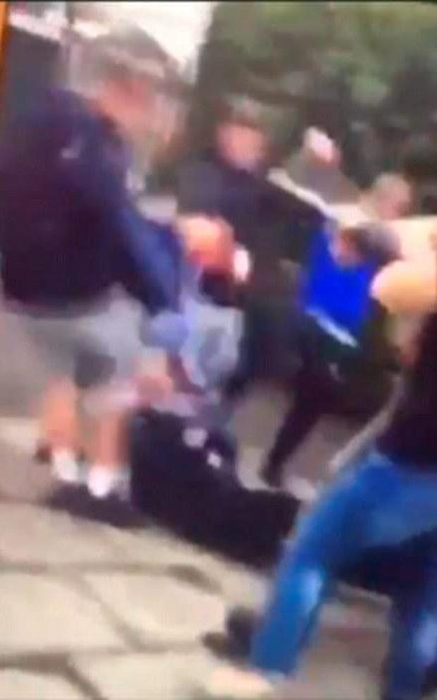 Some of them were armed with sticks as the kicked and punched the person on the floor