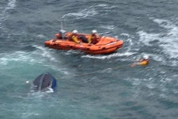 A lifeboat tows the submerged vessel to the harbour.