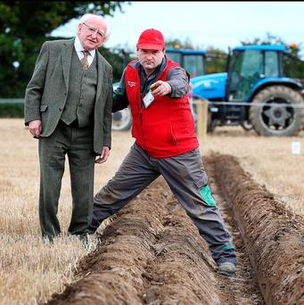 President Michael D. Higgins chats with Dave Mulcahy from Leamcara Cork who is a competitor in the Intermediate Tractor Class alongside his furrow at the National Ploughing Championships in Screggan, Tullamore Co Offaly. Pic Steve Humphreys