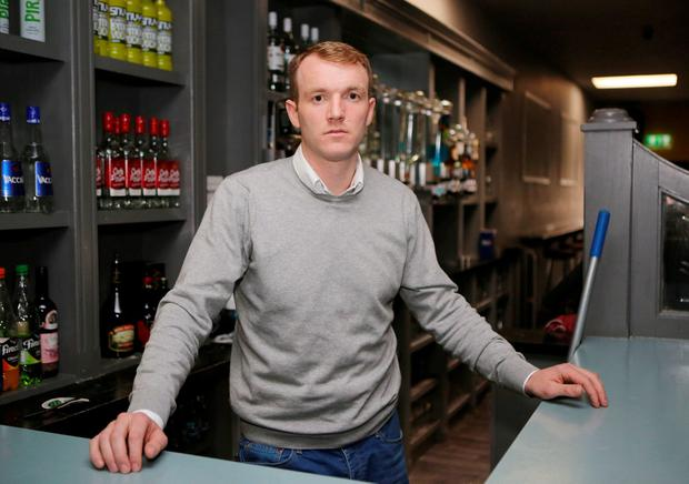 Former Tipperary hurler Lar Corbett behind the bar in his premises in Thurles. Photo: Liam Burke/Press22