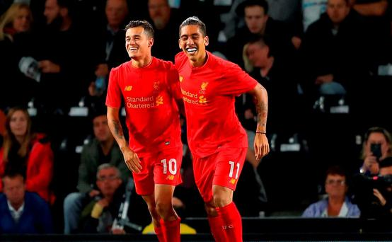 Philippe Coutinho (L) of Liverpool celebrates scoring his team's second goal with Roberto Firmino during the EFL Cup Third Round match between Derby County and Liverpool at iPro Stadium