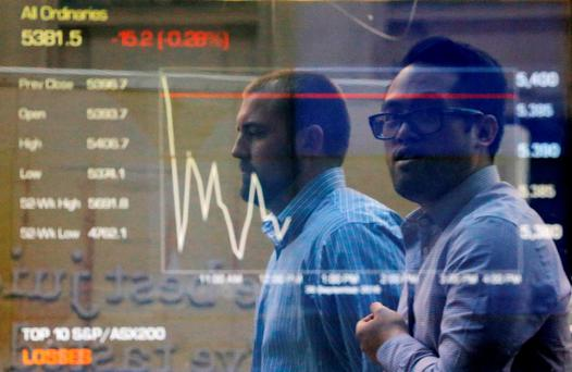 City workers walk past Australia's stock exchange index on an electronic board in Sydney