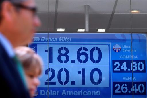 People pass in front of a board displaying the exchange rate for peso and US dollars at a foreign exchange house in Mexico City
