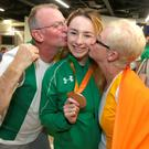 Ellen Keane, from Clontarf, is kissed by her mum Laura and dad Eddie. Photo: Damien Eagers