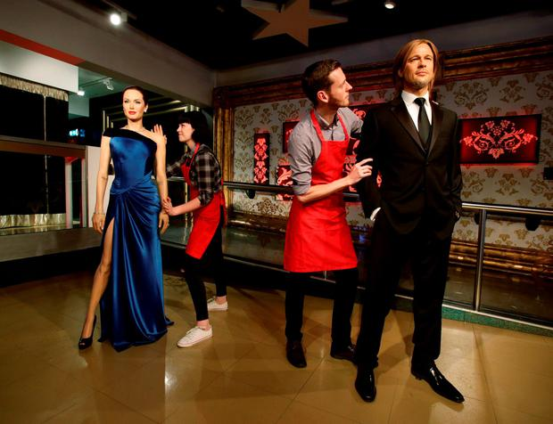 Madame Tussauds' staff separate the waxwork figures of Brad Pitt and Angelina Jolie in London. Photo: Yui Mok/PA Wire