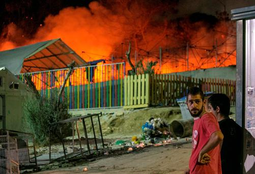 Migrants watch a large fire as it burns inside the Moria refugee camp on the northeastern Greek island of Lesbos. (AP Photo/Michael Schwarz)