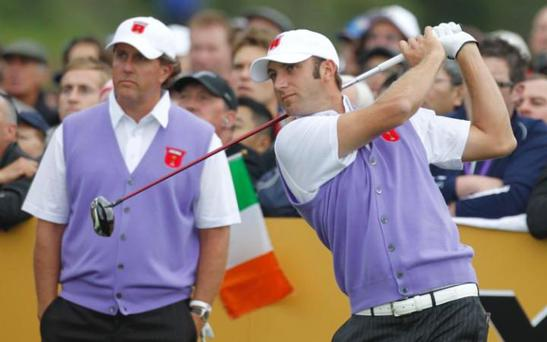 Dustin Johnson plays a tee shot as teammate Phil Mickelson looks on at the 2010 Ryder Cup golf tournament. CREDIT: AP