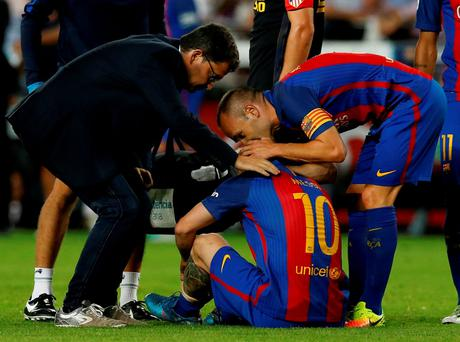 Barcelona's Lionel Messi sits on the pitch injured, next to Andres Iniesta and medical staff member Ricard Pruna. REUTERS/Albert Gea
