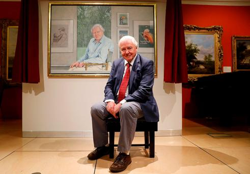 David Attenborough poses next to a portrait of himself by Bryan Organ to mark his 90th birthday at New Walk Museum and Art Gallery in Leicester, Britain. Reuters/Darren Staples