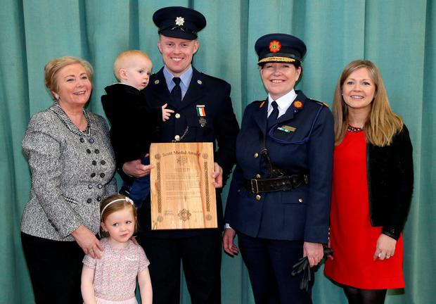 Garda Thomas Dalton, of Leixlip Garda Station, gets a Bronze Scott Medal from Justice Minister Frances Fitzgerald and Garda Commissioner Nóirín O'Sullivan, watched by his proud wife Niamh and children Lucy (3) and Oisin (19 months). Picture Colin Keegan, Collins Dublin.