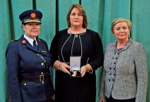 Caroline Donohoe, the widow of Detective Garda Adrian Donohoe, gets a posthumous gold Scott Medal from Justice Minister Frances Fitzgerald and Garda Commissioner Nóirín O'Sullivan. Picture Colin Keegan, Collins Dublin.