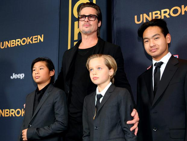 Actor Brad Pitt with three of the six children he has with estranged wife Angelina Jolie – (left to right) Pax Jolie-Pitt, Shiloh Jolie-Pitt, and Maddox Jolie-Pitt on the red carpet in Hollywood in December 2014. Photo by Matt Sayles/Invision/AP