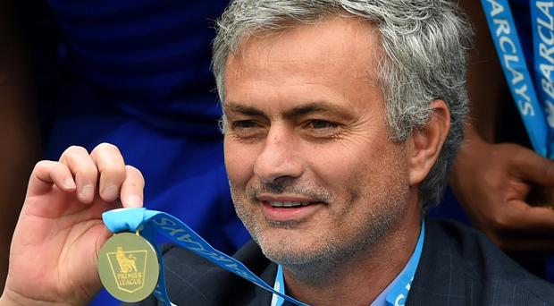 Mourinho poses with his 2014/15 Premier League winners' medal. Getty