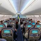 Passengers sitting on their chairs in airplane cabin (stock image)
