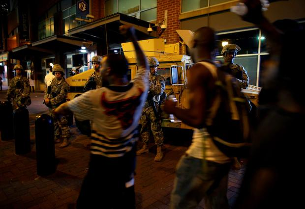 U.S. National guard troops look on as people march through downtown to protest the police shooting of Keith Scott in Charlotte, North Carolina, U.S., September 22, 2016. REUTERS/Mike Blake