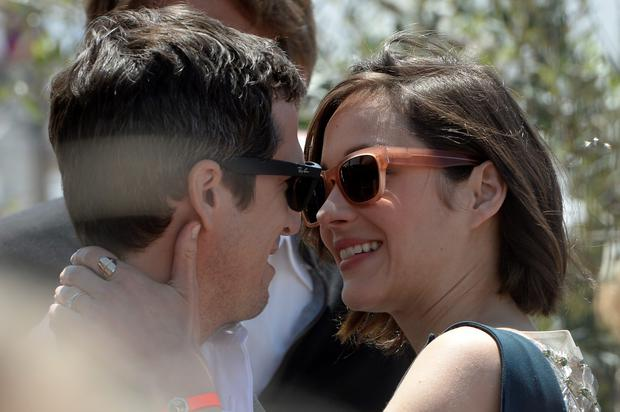 French actress Marion Cotillard (R) hugs her partner French director Guillaume Canet on May 20, 2013 before attending a photocall for the film