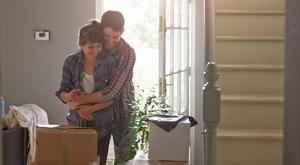 A young professional couple hugging playfully in their home they are surrounded by packing boxes.