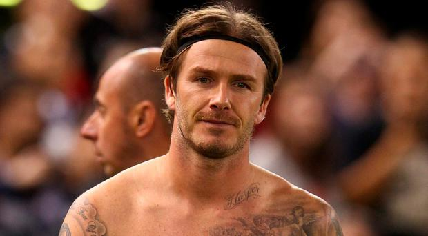 David Beckham shows off some of his body art. Photo: Robert Cianflone/Getty Images)