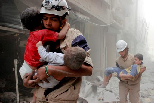 Destruction: Members of the Civil Defence rescue children after what activists said was an air strike by forces loyal to Syria's President Bashar al-Assad in the al-Shaar neighbourhood of Aleppo. Photo: Sultan KitazY